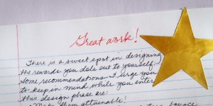 "Gold star sticker on a paper with ""Great work!"" written in red pen"