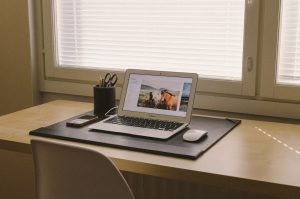 desk near window with clear desktop and open laptop