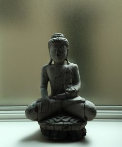 statue of seated buddha on windowsill