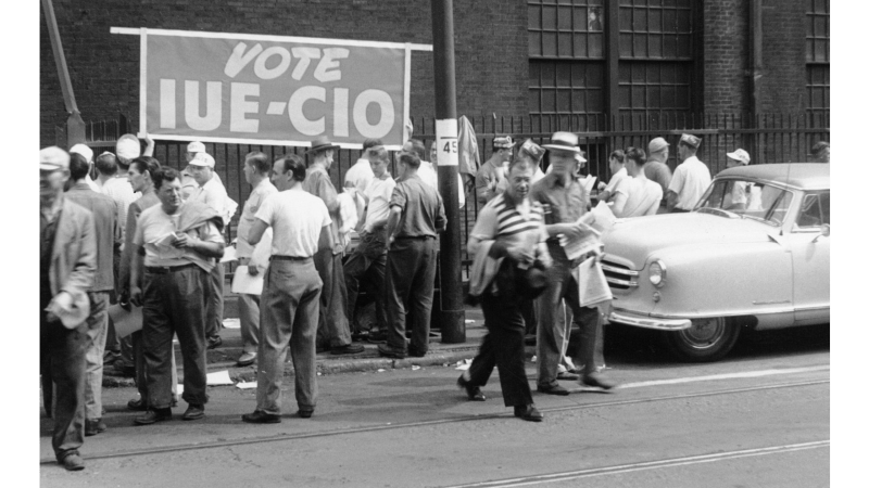 IUE CIO banner on side of Westinghouse plant while workers wait to vote, Pittsburgh, PA, 1949. From University of Pittsburgh digital collection.