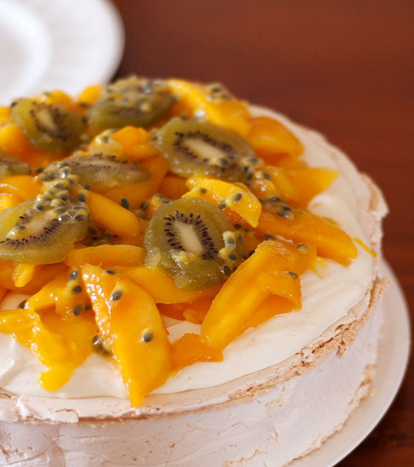 Pavlova topped with whipped cream and mango