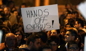 A Cypriot holds a placard outside parliament in Nicosia