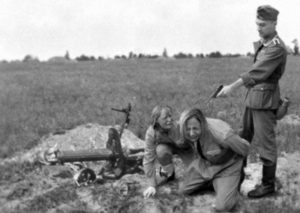 A Nazi soldier gets ready to murder two Soviet Slavic women during Operation Barbarossa, summer 1941. This incident probably took place in the Ukraine or Belarus.