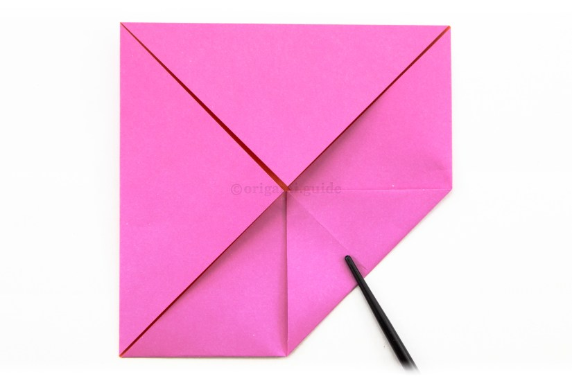 9. For a second time, fold one corner to the middle of the square.