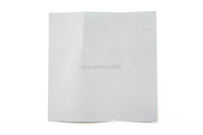5. Place the paper back down on the table. You can see the thirds marked on the top edge.