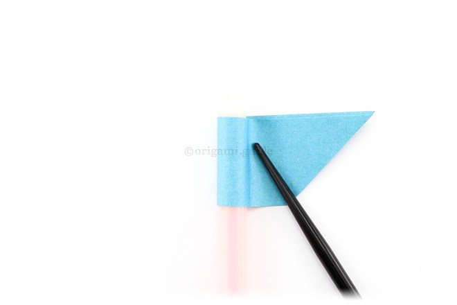 15. Fold the left end over your finger or pen and to the right. Shape the paper around to create a tube.