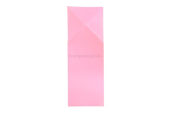 Unfold the previous step and flip the paper over to the other side.