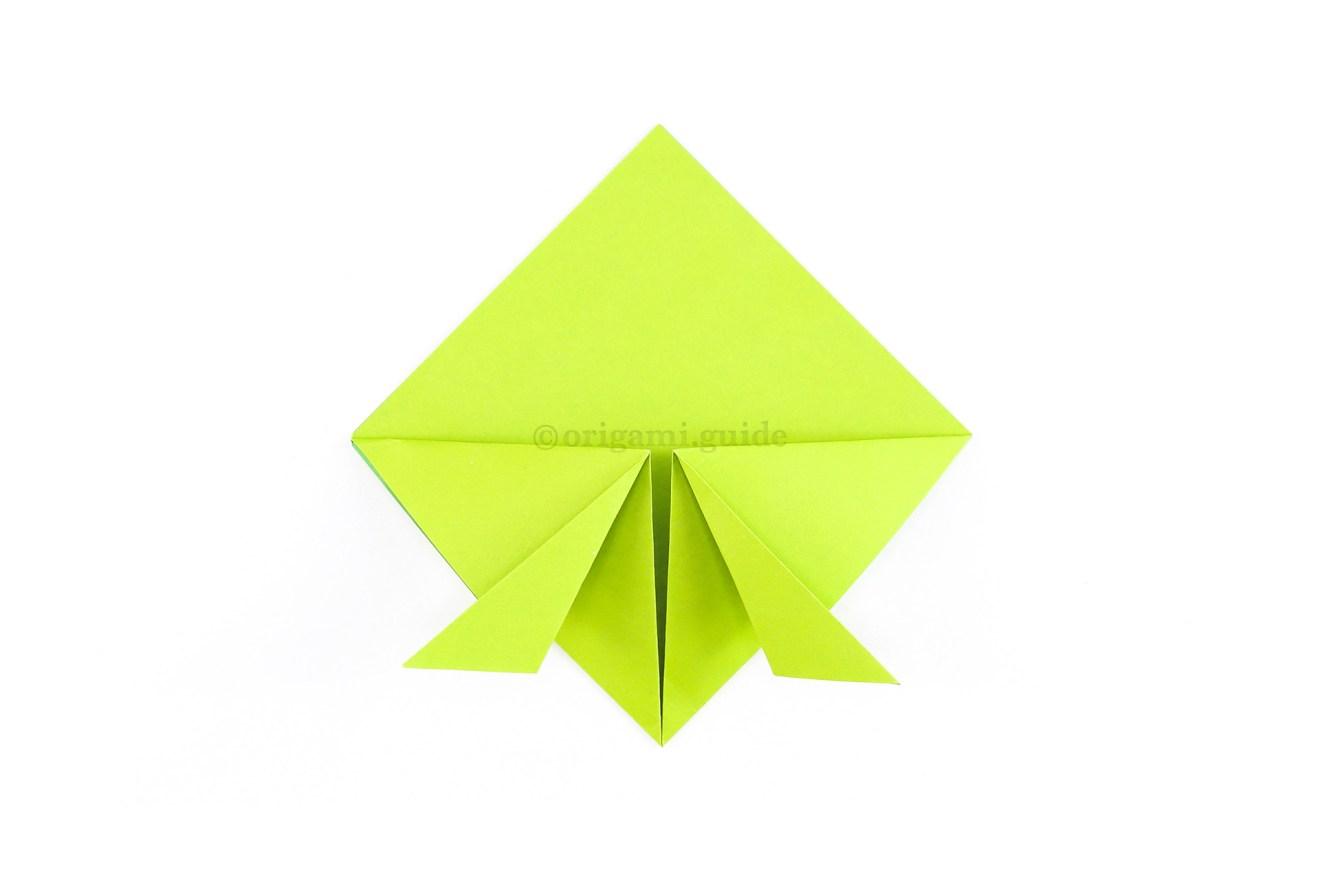 Fold both bottom points diagonally outwards as shown.
