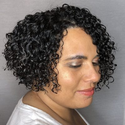 Short, curly, medium density hair cut and styled by curly hair specialists at the Original Moxie Salon.
