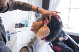 Curly cut and style with edges being performed at the Original Moxie Salon