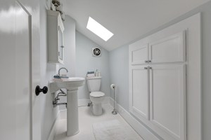 2nd Level Bathroom Remodel with Skylight, Pedestal Sink, Toilet and Eave Storage Cabinet in Light Color Scheme
