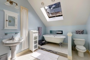 2nd Level Bathroom Remodel with raised Clawfoot Tub, Toilet behind knee wall and Pedestal Sink as well as operable skylight for fresh air and sunlight