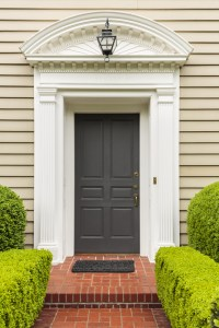 Exterior Remodel with Decorative White Front Portico, Black Door and Paver Walkway