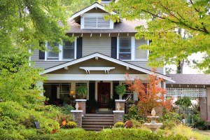 Exterior Remodel of Home with Painted Grey Siding, White Trim, Black Shutters with Large Covered Front Porch all surrounded by trees and landscaping