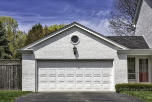 Garage Remodel with White Painted Brick Exterior, White Overhead Door and Octagon Window Centered in Gable