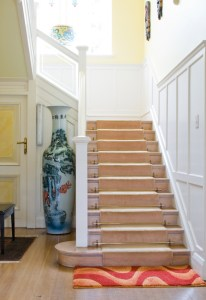Interior Remodel with Wood Stairs, White Painted Handrail and Painted Board and Batten Wainscot in Entryway with Coat Closet below the Stairs