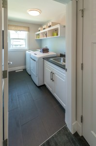 Whole House Remodel with Laundry Room, including White Painted Cabinets, Dark Countertop, Dark Large Format Tile Floor and Open Shelving above Washer and Dryer