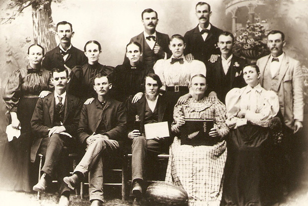 The McLendon family. Thomas Simpson McLendon is in the second row, second to the right. McLendon's parents, Isaac Newton McLendon and Mary Anne Eliza Rowe McLendon, holding copies of the Bible and The Sacred Harp, are seated in the center of the first row.