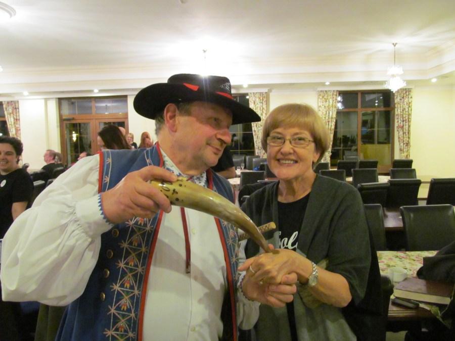 The Kashubian folk dance troupe's ringleader shares snuff with tour group member Linda Thomas. Photograph courtesy of Linda Thomas.