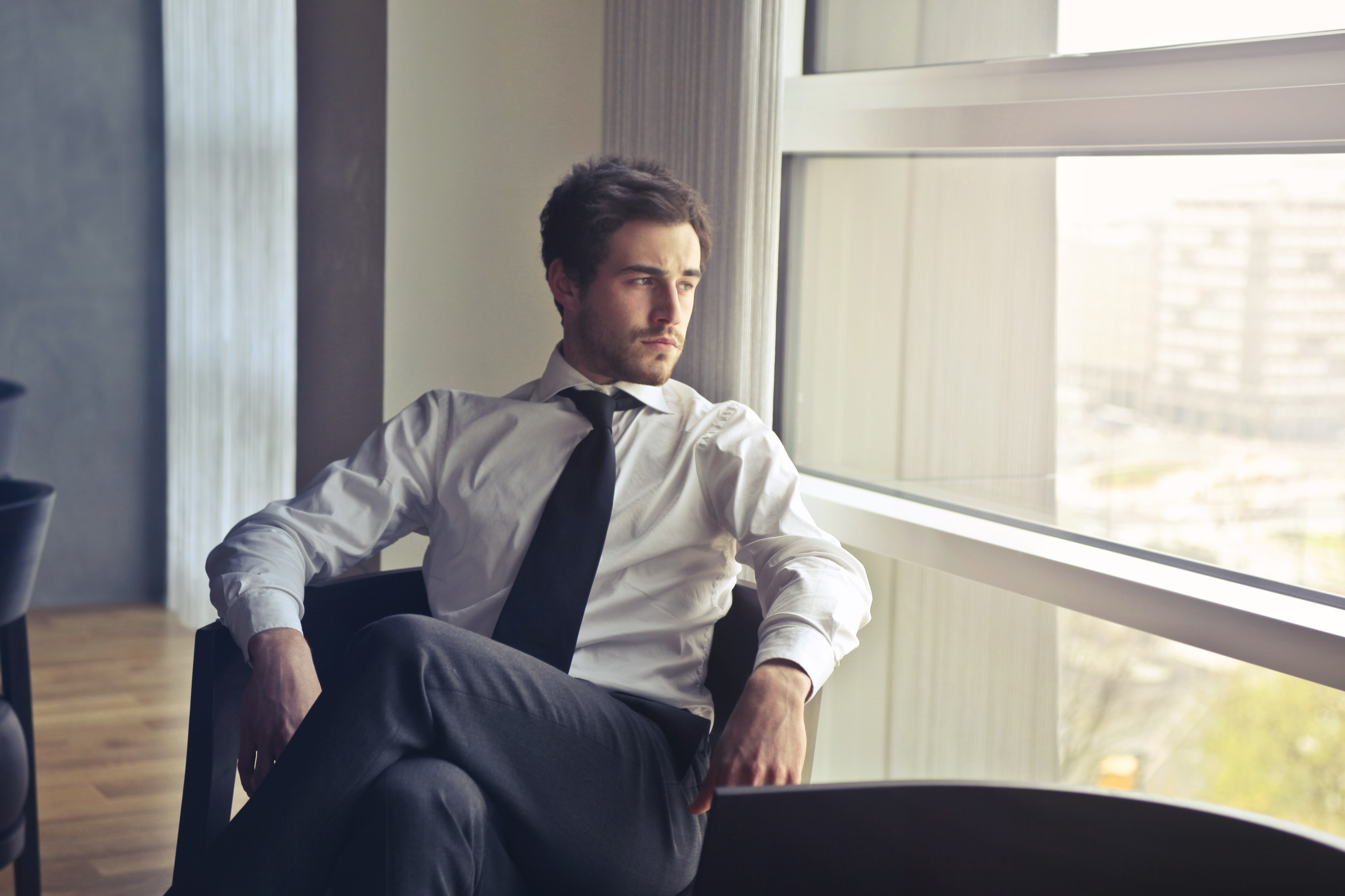 photo of man wearing white shirt and tie in office waiting area