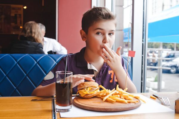 Restaurants where kids eat free in Orlando: image of kid eating a cheap meal