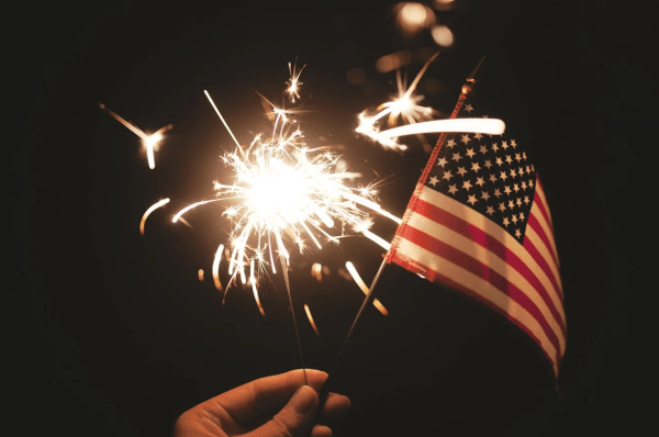 4th of July fireworks Orlando: image of a person with a sparkler and the American flag celebrating the 4th of July