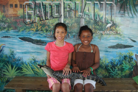 Gatorland Orlando deals: image of two girls holding a baby alligator at Gatorland Orlando theme park