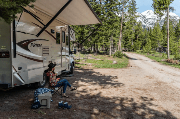 Rent RV Orlando: image of a woman relaxing outside her RV at a state park