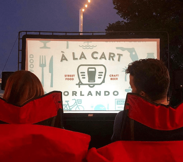 Outdoor movies Orlando: image of a couple watching a free outdoor movie at A La Cart Orlando