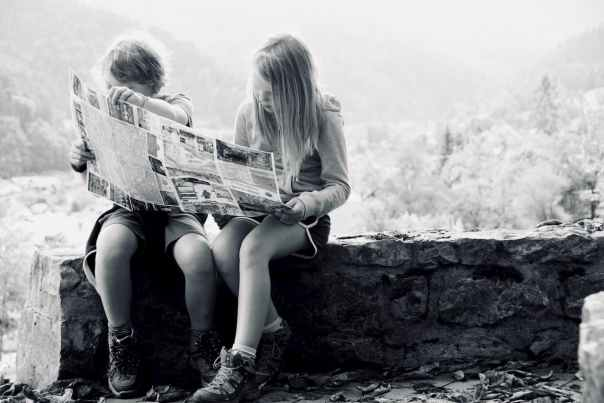 Children reading newspaper.