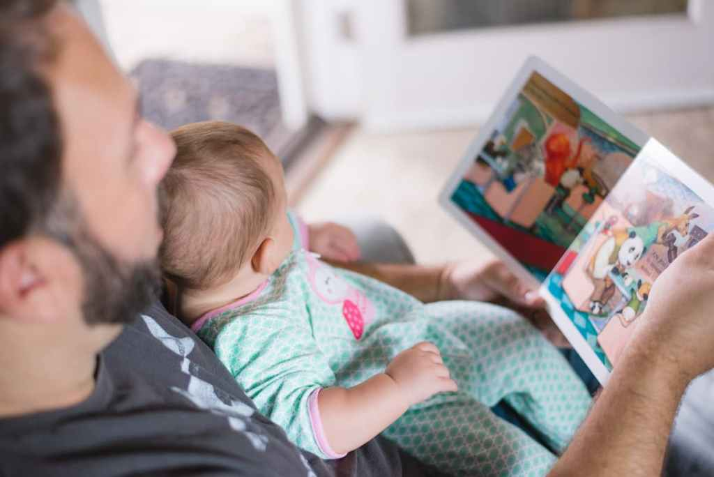 Photo of a person reading a book to a baby.