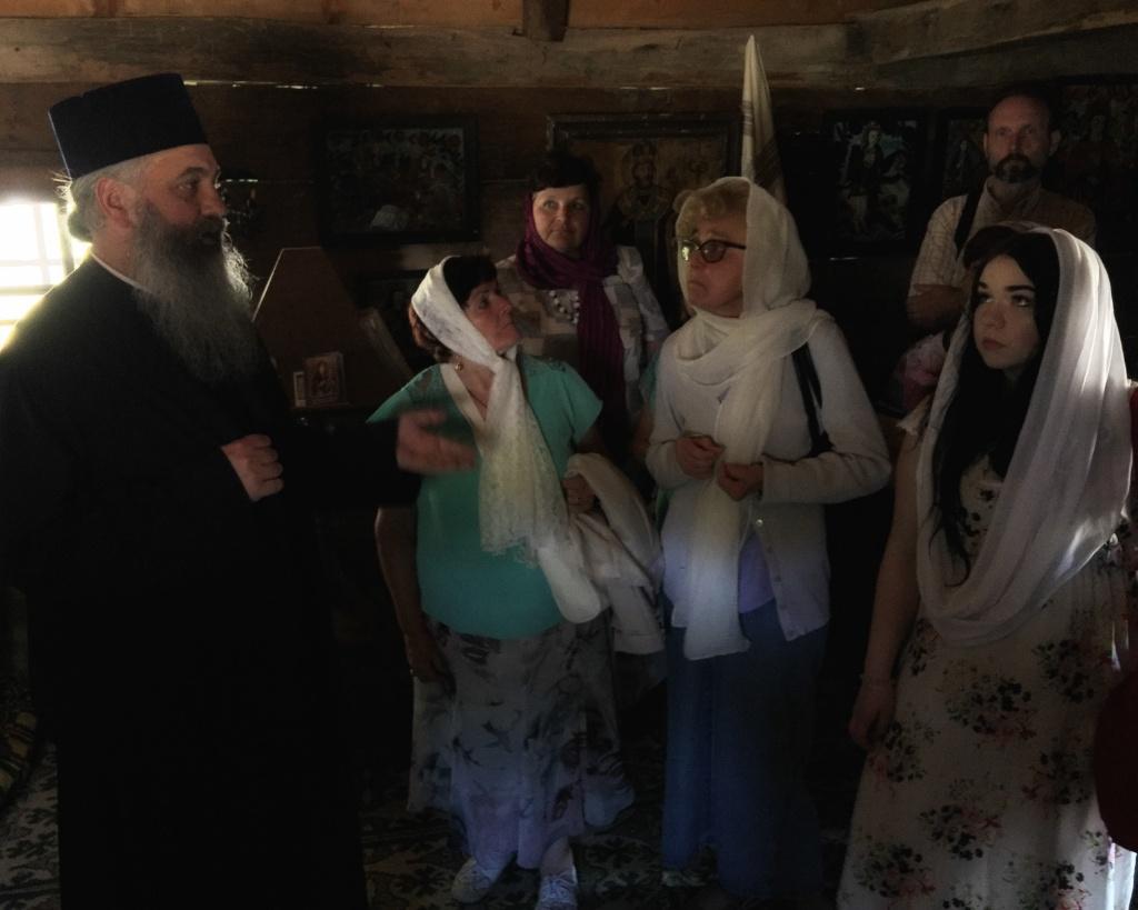 Archimandryta Dumitru Cobzaru i pielgrzymi we wnętrzu drewnianej monasterskiej cerkwi z XVI w.