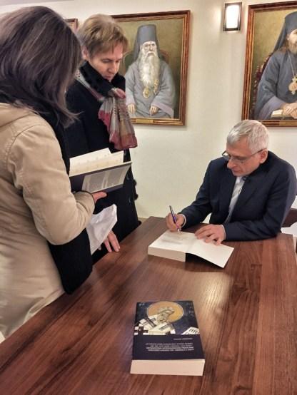 Prof. Leśniewski podpisuje swoją książkę, poświęconą Wielkiemu Kanonowi
