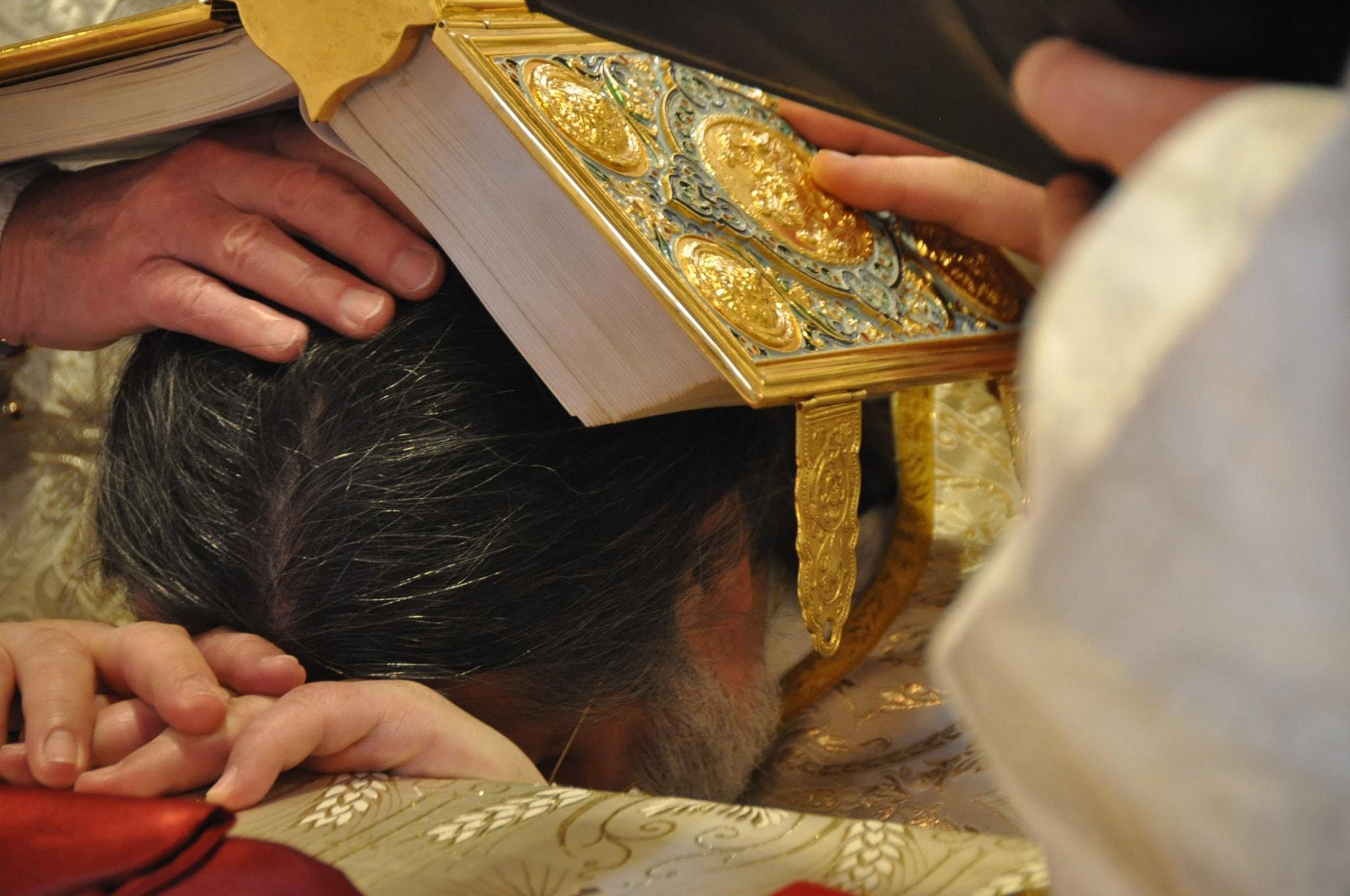 Agenouillé devant l'autel, l'évangéliaire ouvert sur sa tête, le nouvel évêque est consacré (© 2019 Alex Romash).