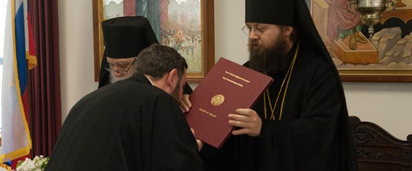 Holy Trinity Seminary student recieving bachelor of theology degree from his grace, Bishop Irenei, at the 2017 commencement ceremony.