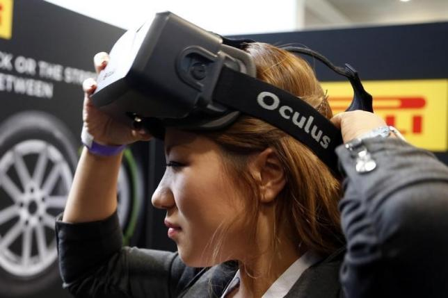 A woman puts on an Oculus virtual reality headset  during preparations for the 2014 LA Auto Show in Los Angeles