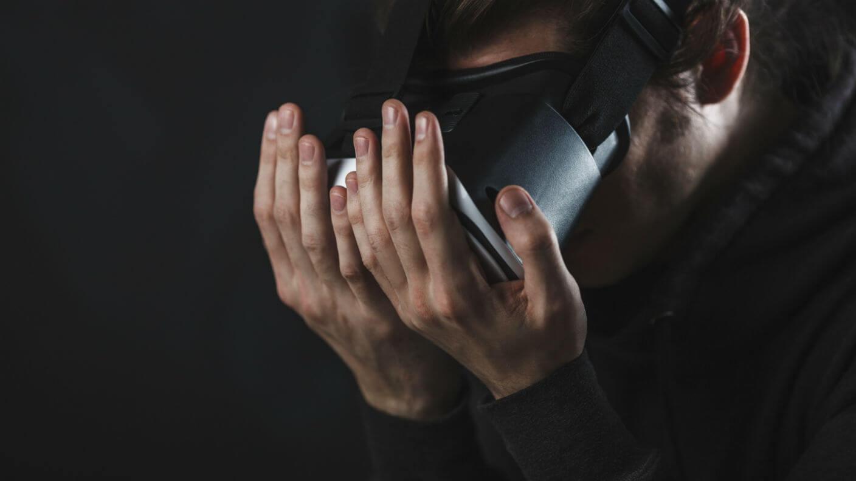 man-staring-at-hands-virtual-reality-075627439