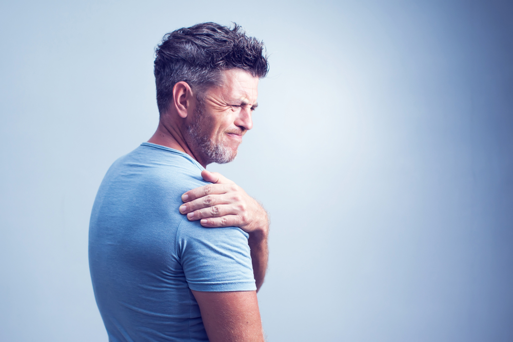man experiencing shoulder pain on grey background