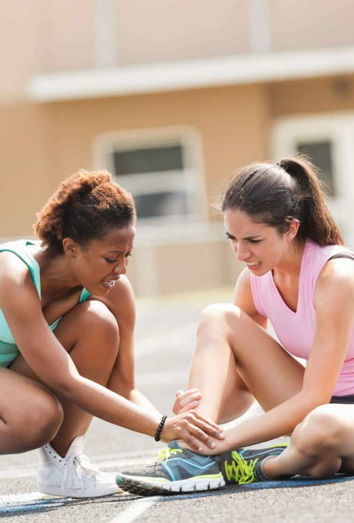 Friend checking on injured athlete during track meet race, possible fracture or trauma