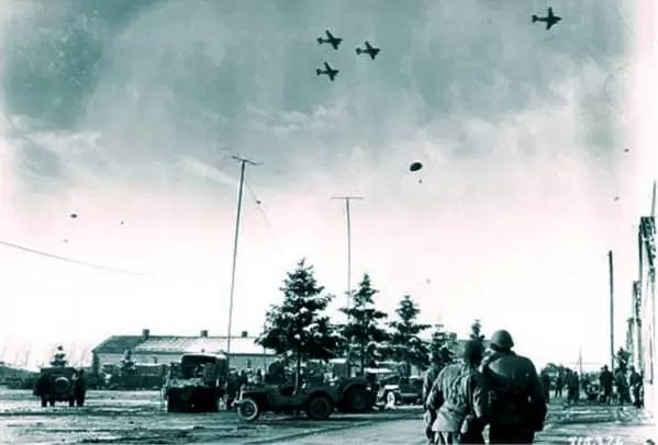 Saveznički avioni izbacuju preko potrebne namirnice, medicinski materijal i municiju opkoljenim padobrancima kod Bastonja