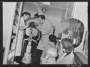 Russel Lee. FSA Farm Security Administration dentist and migrant child in the FSA dental trailer at the FSA camp for farm families Caldwell Idaho