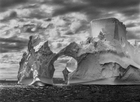 05-1-450/43. Iceberg between Paulet Island and the South Shetland Islands on the Antarctic Channel. At sea level, earlier flotation levels are clearly visible where the ice has been polished by the ocean's constant movement. High above, a shape resembling a castle tower has been carved by wind erosion and detached pieces of ice. The Antarctic Peninsula. January and February 2005.
