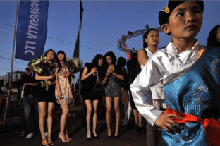 © Mark Leong. A traditional child acrobat stands before a line of fashion models at a boy-band pop concert sponsored by the formerly Soviet-run APU vodka factory. In Ulaanbaatar, the abrupt societal shift makes for plenty of scenes of collision between the centuries-old and the brand new.