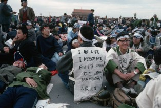 """ca. May 10-16, 1989, Beijing, China --- A young student protester in Tiananmen Square wears a sign written in English, which reads: """"I love life, I need food, but I'd rather die without democracy."""" --- Image by © Peter Turnley/Corbis"""