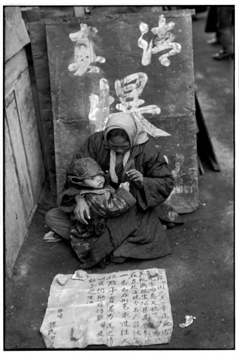 """CHINA. Pekín. De diciembre de 1948. Una madre acurruca a su bebé cerca de ella, con la esperanza de que su letrero le ayudará. Una refugiada en la gran ciudad. Ha escrito """"Me llamo Sun. Mi marido murió por una enfermedad. Somos ajenos a este pueblo. No tenemos medios para vivir. Me veo obligada a pedir caridad a quienes tienen buen corazón""""."""