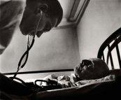 El Dr. Ceriani comprueba la presión arterial de Thomas Mitchell, de 85 años, que llegó al hospital con una pierna gangrenada. Sabiendo que Mitchell podría no ser lo suficientemente fuerte como para soportar la amputación, Ceriani había estado posponiendo la cirugía.