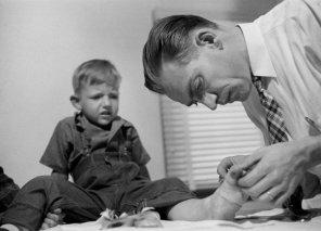 No publicada en LIFE. el Dr. Ceriani revisa el pie de un pequeño que pisó vidrio roto.