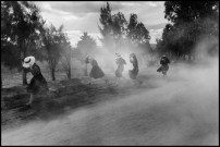 MEXICO. Durango. Young Mennonite women fleeing a cloud of dust. 1994.