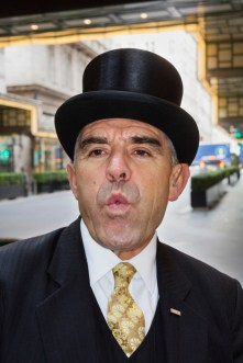 GB. England. London. The Savoy Hotel. Doorman, Tony Cortegaca whistling for a cab. 2016.