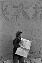 """CHINA. 1965. Farmer of the Henan. At the exit of the canteen, she reads """"The young China """". On the front page: """" successful Explosion of the second atom bomb """"."""
